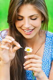 Woman wonders on flower. Young lovely smiling woman wonders on flower, tearing petals, close-up Royalty Free Stock Photo