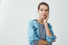 Woman wonders in her thoughts. Indoor portrait of charming sensual girl with bun hairstyle holding palm on cheek and. Looking aside at copy space while dreaming Royalty Free Stock Photo