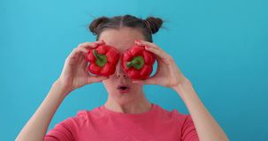 Woman wonders holds pepper in her hands like eyes. Smiling girl covering his eyes with paprika peppers. Happy girl with fresh vegetables wonders. Close up girl stock video footage