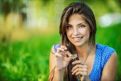Woman wonders, tearing petals on Stock Image