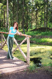 Woman in wood on bridge at pond Stock Photo