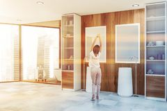 Woman in wooden bathroom with cabinets. Young woman standing in luxury bathroom with wooden walls, large window, comfortable bathtub and double sink with mirrors stock images