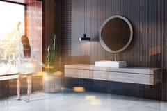 Woman in wooden bathroom corner, sink. Woman standing in corner of modern bathroom with wooden and beige walls, concrete floor, white sink on wooden countertop stock photography