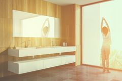 Woman in wooden bathroom with double sink. Woman in pajamas standing near panoramic bathroom window. Wooden walls and double sink. Luxury house interior. Toned stock image