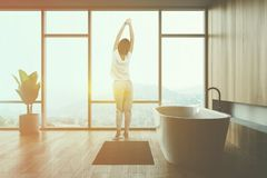 Woman in wooden bathroom interior. Rear view of woman in pajamas standing in minimalistic bathroom interior with wooden walls, panoramic windows and rug near stock photo