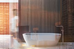 Woman in wooden bathroom interior, sink and tub. Woman walking in interior of modern bathroom with wooden and beige walls, concrete floor and white bathtub royalty free stock images
