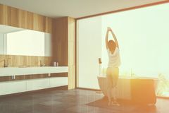 Woman in wooden bathroom, tub and sink. Woman in pajamas standing in modern wooden bathroom with double sink and white bathtub. Toned image double exposure royalty free stock photo