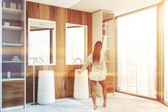 Woman in wooden bathroom with two sinks. Rear view of woman standing in luxury bathroom with wooden walls, large windows and double sink with mirrors. Toned stock image