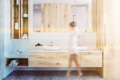 Woman in wooden bathroom, white double sink. Woman wlakind in white and wooden wall bathroom interior with a concrete floor, a double sink with a long horizontal royalty free stock photo