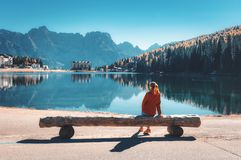 Woman on the wooden bench on the coast of the lake. Young woman sitting on the wooden bench on the coast of Misurina lake at sunset in autumn. Dolomites, Italy stock images