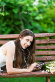 Woman on wooden bench with digital tablet. Portrait of young woman outdoors Stock Image
