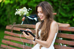 Woman on wooden bench with digital tablet Royalty Free Stock Photos
