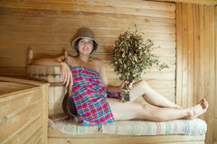 Woman  on wooden bench in sauna Stock Photo