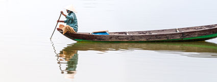 Woman on wooden boat in river in Vietnam, Asia. Woman in conical hat sitting on canoe and rowing. Traditional asian boat made of wood. Person holding paddle in Stock Photos