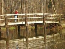 Woman on wooden bridge Stock Images