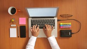 Woman at wooden desk typing on laptop with mobile phone, coffee cup, keys, glasses, notebook, external drive and markers stock footage