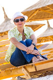 Woman on wooden lounge chair on beach Stock Photo