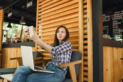 Woman in wooden outdoors street summer coffee shop sitting with laptop pc computer, doing selfie shot on mobile phone stock images