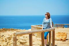 Woman at wooden walkway along the coastline in Algarve region Stock Images