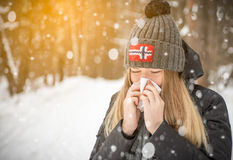 The woman in the woods in the snowing scarf sneezing and using a tissue, portrait, bubo cap with  flag of Norway Stock Photo