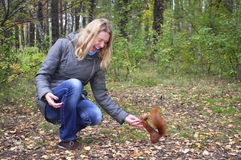 Woman in the woods squirrel bites the hand. Stock Images