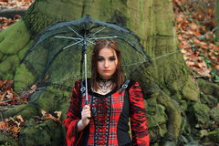Woman in the woods with umbrella. Beautiful brunette woman with umbrella wearing a red dress standing in the woods in front of a tree Stock Photo