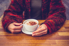 Woman in wool jumper drinking coffee on cold day Royalty Free Stock Image