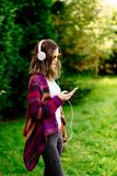 Woman in woolen sweater listening to music in park Royalty Free Stock Images