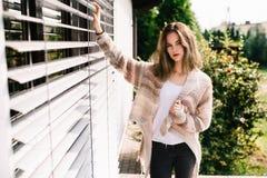 Woman in woolen sweater posing on terrace. Portrait of a young woman in woolen sweater posing on terrace Stock Photo