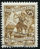 Woman worcing in the field. RUSSIA KALININGRAD, 12 NOVEMBER 2016: stamp printed by Yugoslavia, shows a woman worcing in the field, circa 1950 royalty free stock image