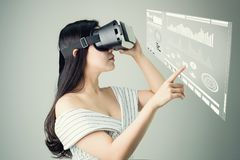 Woman wore a virtual reality headset that simulates, And touch screen technology graph. Stock Image
