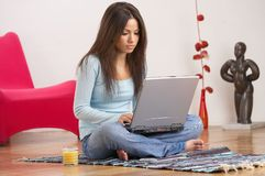 Woman at work. Young lady with long dark brown hair, blue top, jeans and laptop, sitting on the floor of her living room Stock Image