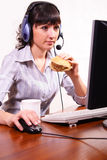 Woman at work. Young woman using computer and holds a sandwich in a hand Royalty Free Stock Images