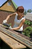 Woman and work. Woman with tool. Reparation window in garden Stock Photos