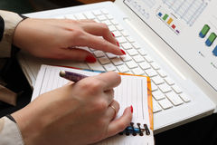 Woman in work. A woman works on a computer and does records in a notebook. Diagram on a screen. Brightly red nails on a hands. Her nails reflected on a screen stock photos
