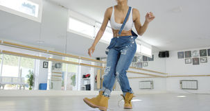 Woman in work boots and overalls dancing. In a studio as seen from a low angle view royalty free stock photos
