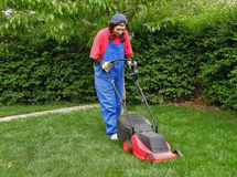 A woman in work clothes cutting the grass Royalty Free Stock Photo
