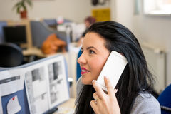 Woman at work gives to customers information using mobile phone. And smiling Royalty Free Stock Photo