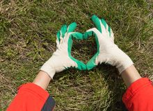 Woman in work gloves shows sign heart, on grass background Stock Photo