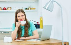 Woman work at home kitchen with laptop. And drink coffee royalty free stock image