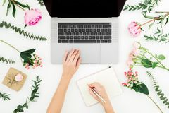 Woman work with laptop. Workspace with female hands, laptop, notebook and pink flowers on white background. Top view. Flat lay. Woman work with laptop. Workspace royalty free stock photo