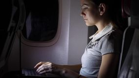 Woman work at notebook in airliner, night flight concept. Woman work at notebook in airliner, night flight. Girl type on laptop at dark airplane cabin stock footage