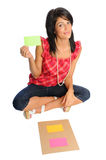 Woman work on a project. Attractive hispanic woman holding bright index cards on a white background Stock Image
