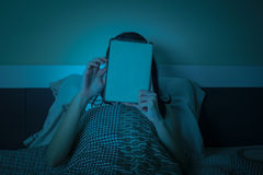 Woman work with tablet or computer on the bed at night Stock Photography