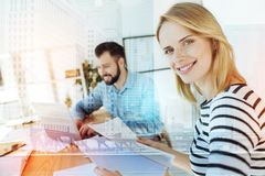 Pretty nice-looking woman working and looking straight. Woman at work. Young pretty nice-looking women working in the office with the documents near her Royalty Free Stock Image
