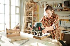 Woman by workbench. Young woman in workwear and protective eyeglasses holding by fretsaw handles while processing wooden board Stock Photo