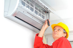 Woman worker adjusting air conditioner system Royalty Free Stock Photo