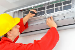Woman worker adjusting air conditioner system Stock Image