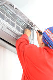 Woman worker adjusting air conditioner system Stock Photography