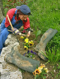 Woman (worker) cultivated flower gardens. Attractive brunette woman (worker in work clothes (coveralls) with blue cap on head cultivated with flower gardens. She stock images